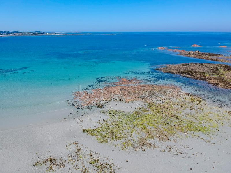 Guernsey island & white sand  beach, blue transparent water and rocks royalty free stock photo