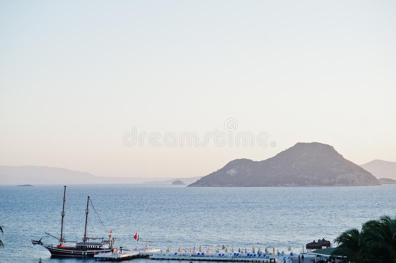 Aerial view of wooden pier with harbor, pirate tourist ship and marina in Turkey resort near Bodrum in sunset light stock image