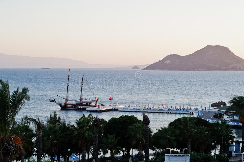 Aerial view of wooden pier with harbor, pirate tourist ship and marina in Turkey resort near Bodrum in sunset light.  royalty free stock photo