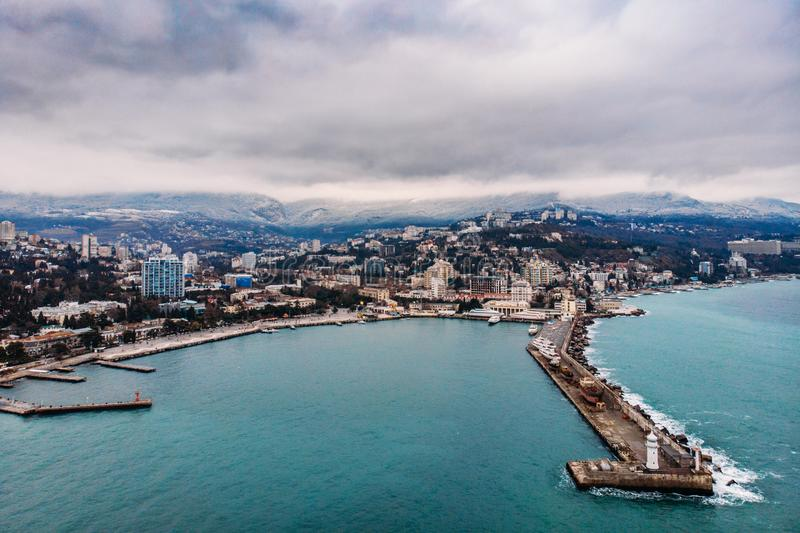 Aerial view of Yalta embankment from drone, old Lighthouse on pier, sea coast landscape and city buildings on mountains, Crimea royalty free stock photos