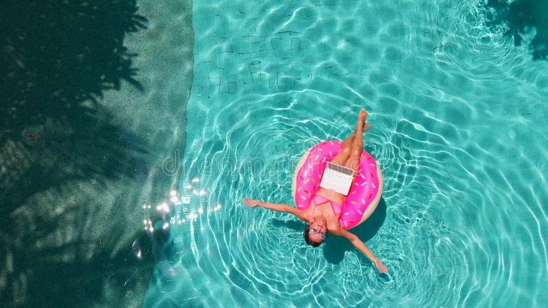 Aerial view of a young brunette woman swimming on an inflatable big donut with a laptop in a transparent turquoise pool. royalty free stock photo