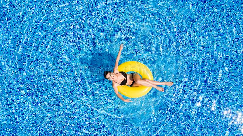 Aerial view of young brunette woman swimming on the inflatable big yellow in the pool. Top view of slim lady relaxing on her holid royalty free stock photos