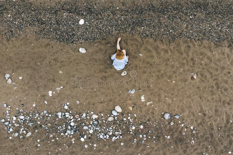 Aerial view of young woman sitting on beach royalty free stock photos