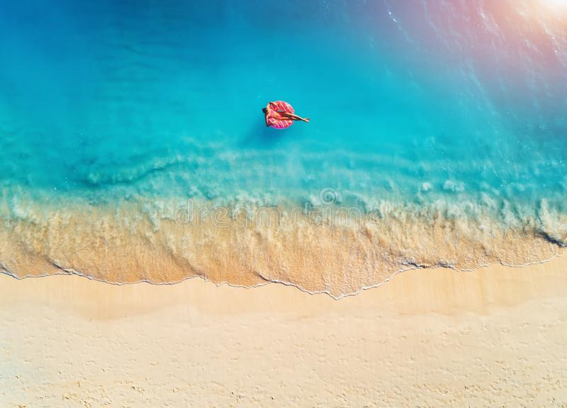 Aerial view of a young woman swimming with the donut swim ring. In the clear blue sea with waves at sunrise in summer. Tropical aerial landscape with girl stock photography