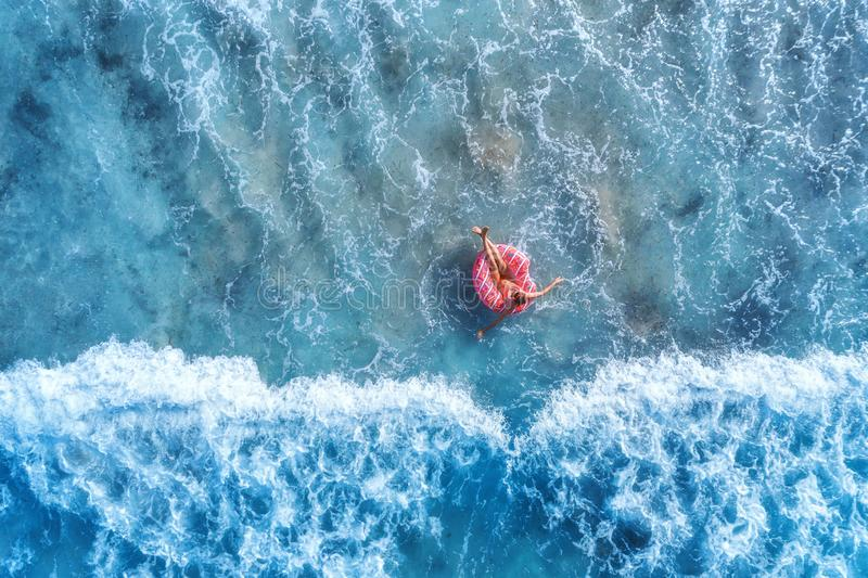 Aerial view of a young woman swimming with the donut swim ring stock image