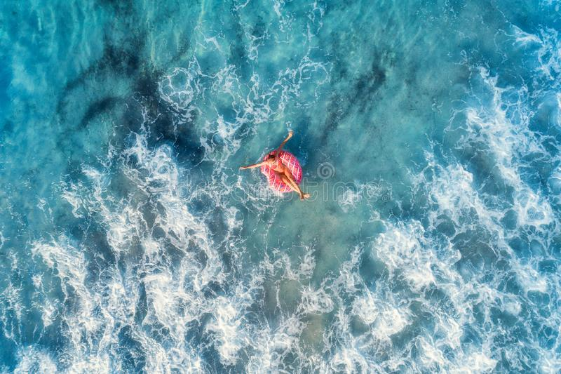 Aerial view of a young woman swimming with the donut swim ring stock photos