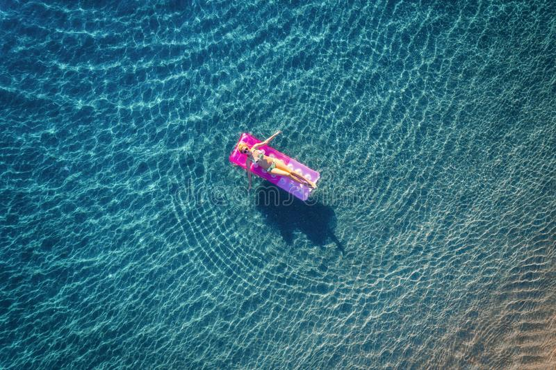 Aerial view of young woman swimming on the pink inflatable mattr stock image