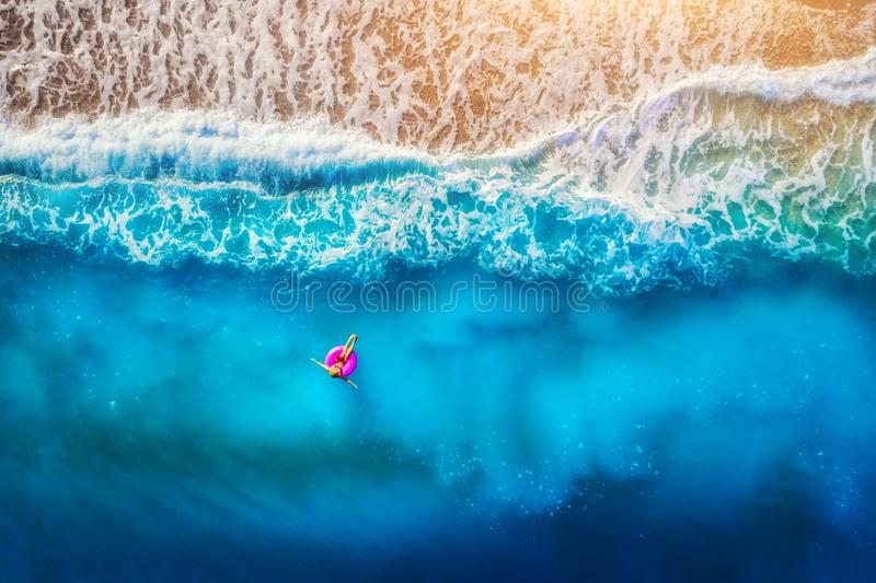 Aerial view of young woman swimming on the pink swim ring. Aerial view of woman swimming on the pink swim ring in the transparent sea in Oludeniz. Summer stock photo