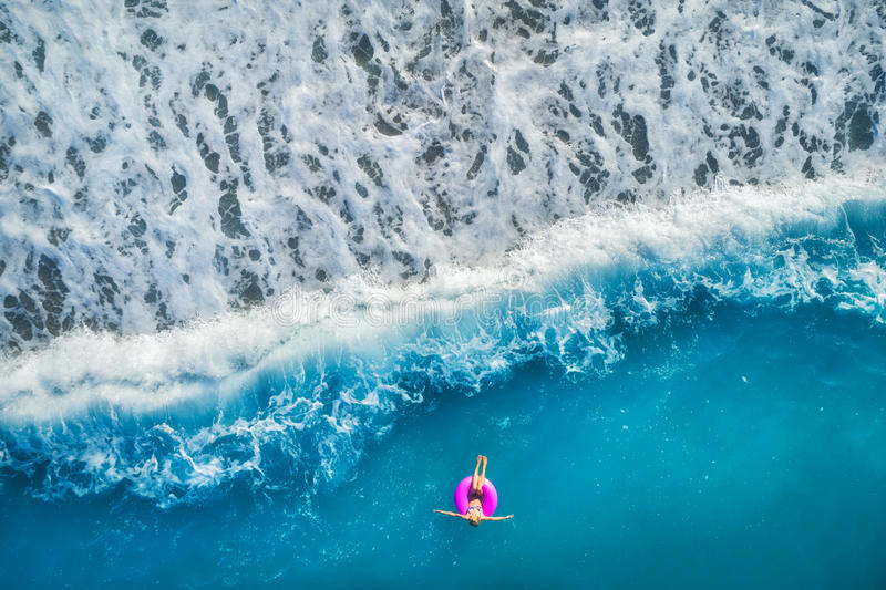 Aerial view of young woman swimming on the pink swim ring. In the transparent turquoise sea in Oludeniz,Turkey. Summer seascape with girl, beautiful waves stock photography