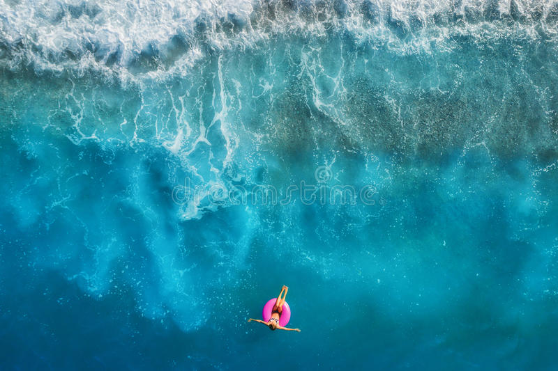 Aerial view of young woman swimming on the pink swim ring. In the transparent turquoise sea in Oludeniz,Turkey. Summer seascape with girl, beautiful waves royalty free stock photography