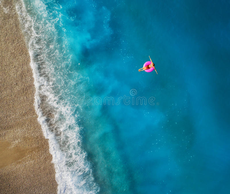 Aerial view of young woman swimming on the pink swim ring. In the transparent turquoise sea in Oludeniz,Turkey. Summer seascape with girl, beautiful waves, blue royalty free stock photo