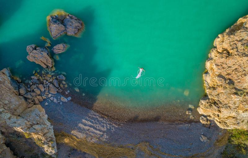 Aerial view of a young woman wearing a white dress on the rocks. Summer seascape with a girl, beach, beautiful waves, rocks, blue royalty free stock images