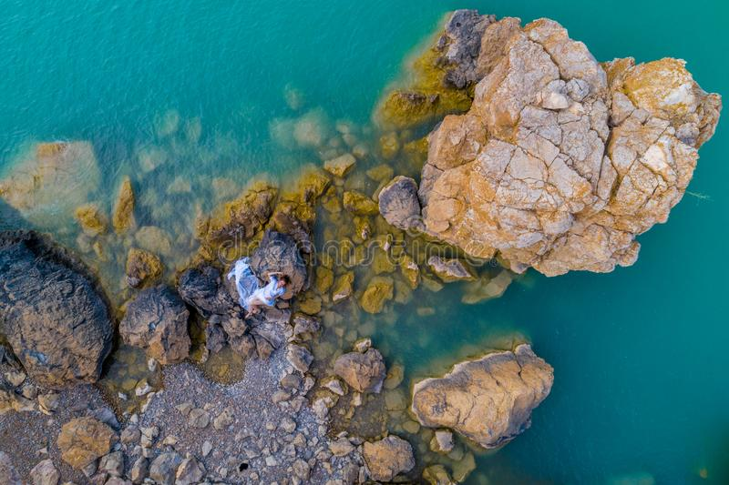 Aerial view of a young woman wearing a white dress on the rocks. Summer seascape with a girl, beach, beautiful waves, rocks, blue royalty free stock photography