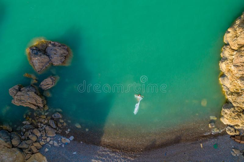 Aerial view of a young woman wearing a white dress on the rocks. Summer seascape with a girl, beach, beautiful waves, rocks, blue royalty free stock photo