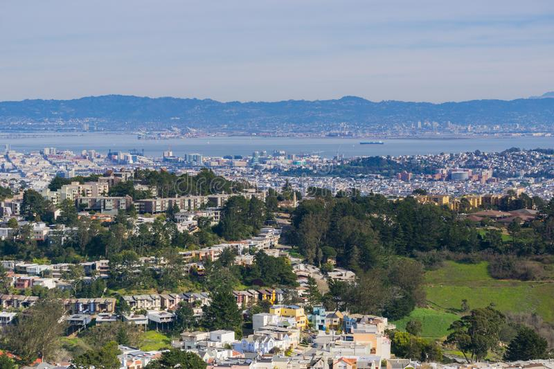 Aerial views of residential areas of San Francisco, San Francisco bay, Oakland and industrial areas in the background, California royalty free stock photo