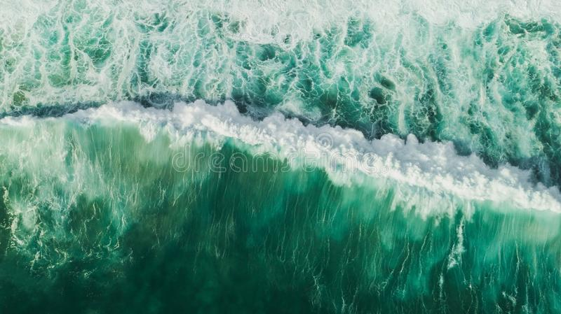 Aerial wave background. Drone shot from above. Aerial wave background. Drone shot directly from above, green turquoise color, huge waves. Empty space royalty free stock photo
