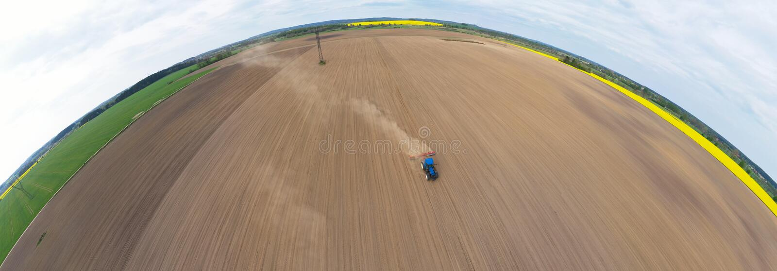 Aerial wide curved panoramic view on blue tractor pulling a plow, preparing a soil for seed sowing, tractor making dirt cloud. stock images