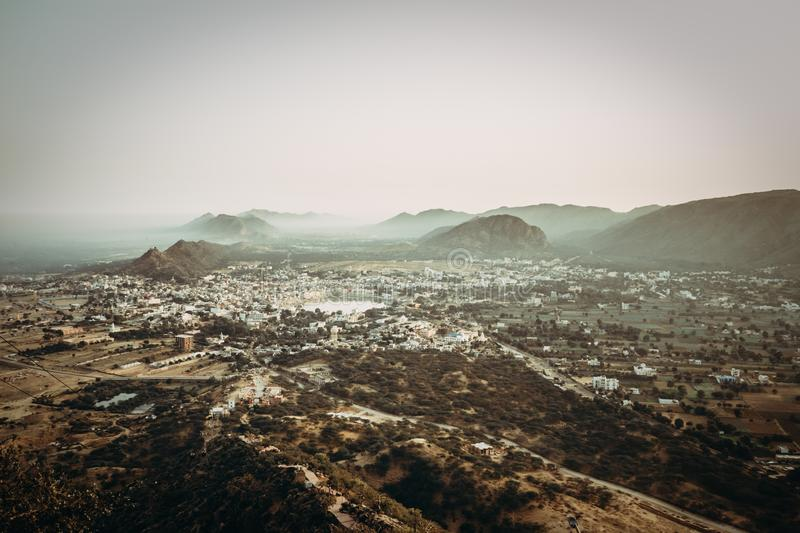 Aerial wide shot of a suburban town in the middle of a large valley with rocky mountains royalty free stock image