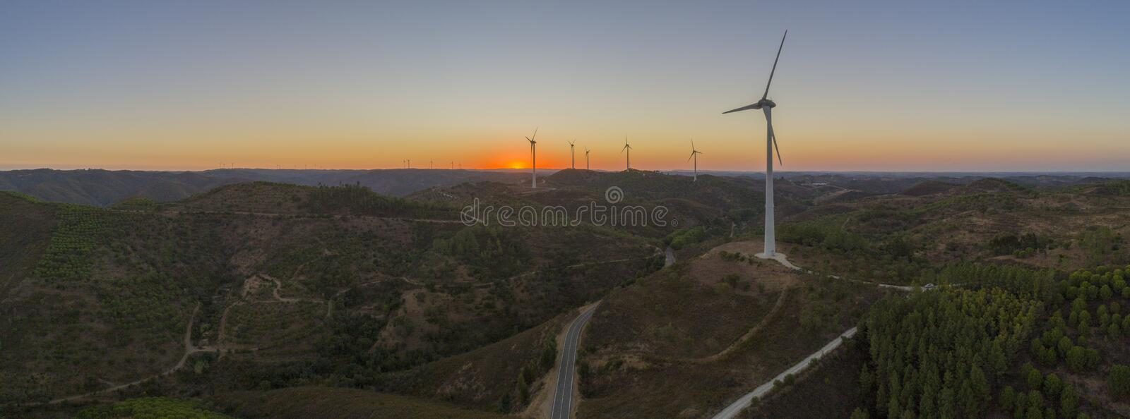 Aerial Wind farm turbines silhouette at sunset. Clean renewable energy power generating windmills. Algarve countryside. Portugal royalty free stock images