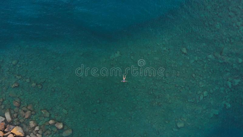 AERIAL: woman floating on blue water surface, swimming in transparent mediterranean sea, top down view, summer vacation concept.  stock images