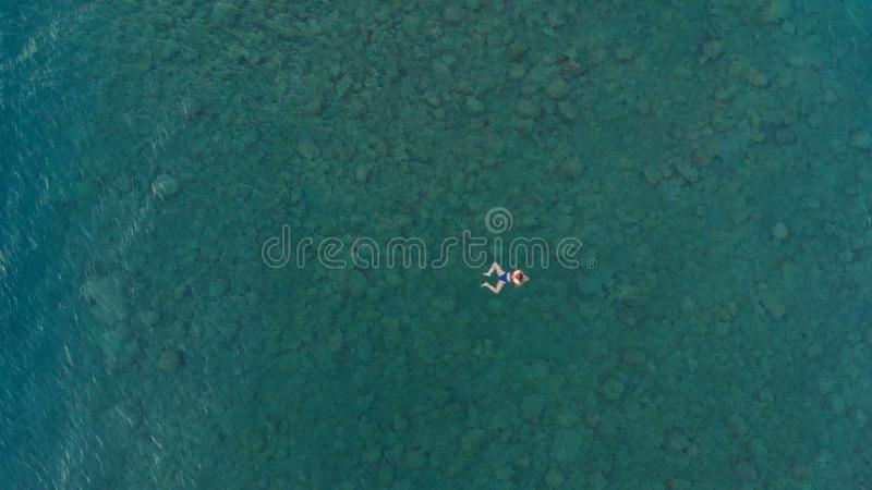AERIAL: woman floating on blue water surface, swimming in transparent mediterranean sea, top down view, summer vacation concept.  royalty free stock images