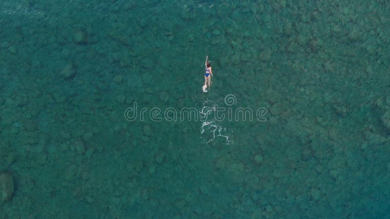 AERIAL: woman floating on blue water surface, swimming in transparent mediterranean sea, top down view, summer vacation concept.  stock photo