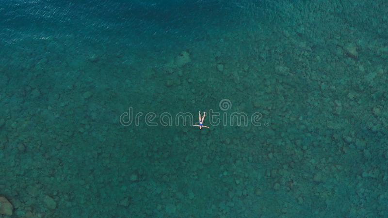 AERIAL: woman floating on blue water surface, swimming in transparent mediterranean sea, top down view, summer vacation concept.  royalty free stock photos