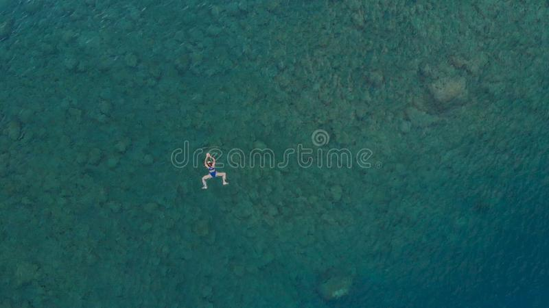 AERIAL: woman floating on blue water surface, swimming in transparent mediterranean sea, top down view, summer vacation concept.  royalty free stock image