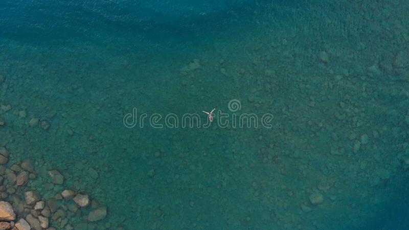AERIAL: woman floating on blue water surface, swimming in transparent mediterranean sea, top down view, summer vacation concept.  stock photos