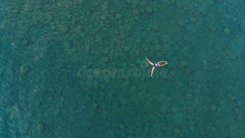 AERIAL: woman floating on blue water surface, swimming in transparent mediterranean sea, top down view, summer vacation concept.  stock photography