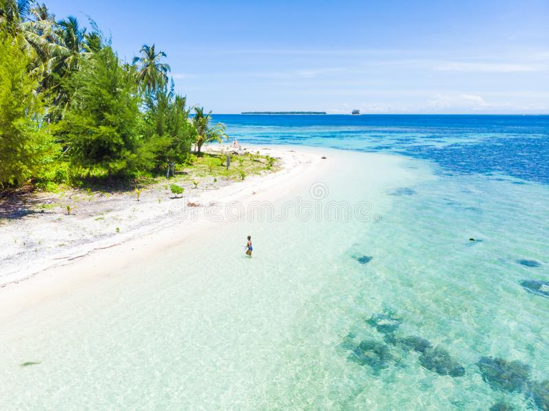 Aerial: Woman getting out of caribbean sea turquoise water tropical coral reef walking on white sand beach. Banyak Islands Sumatra royalty free stock photo