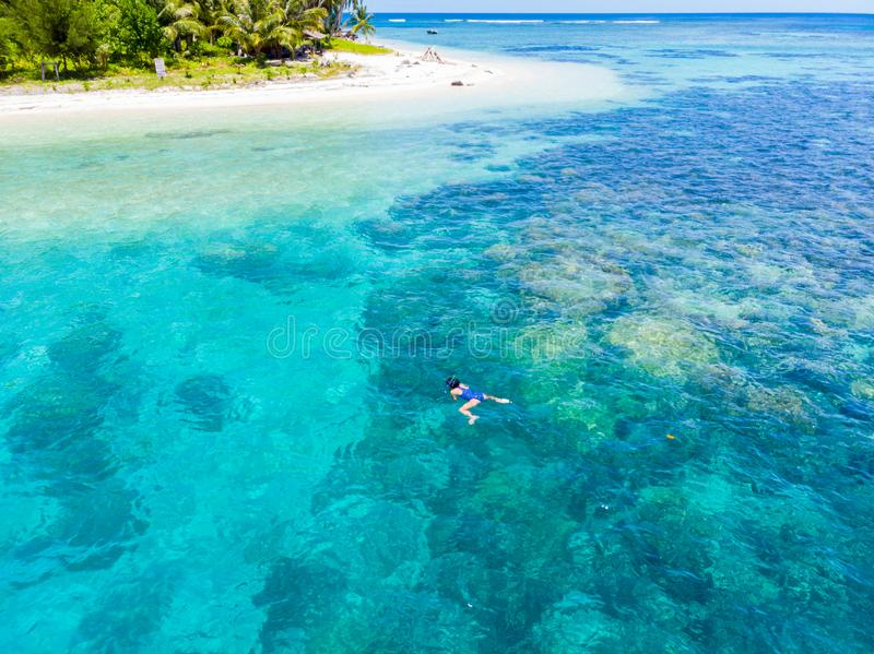 Aerial woman snorkeling on coral reef tropical caribbean sea, turquoise blue water. Indonesia Banyak Islands Sumatra, tourist royalty free stock image