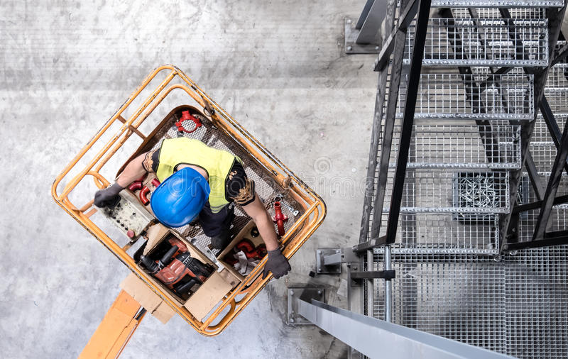 Aerial of a worker on a cherry picker. Aerial of a worker with blue hardhat on a cherry picker royalty free stock images