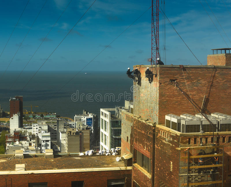 Aerial workers on tall building. Tradesmen working on repairing old red brickwork on a tall building in Montevideo overlooking the Rio del Plata stock images