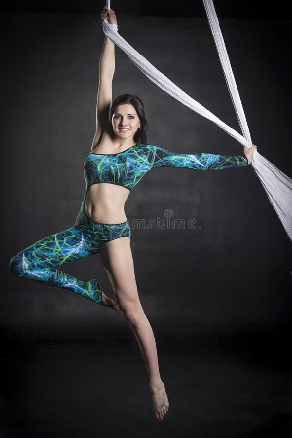 Aerialist doing tricks on silks stock photo