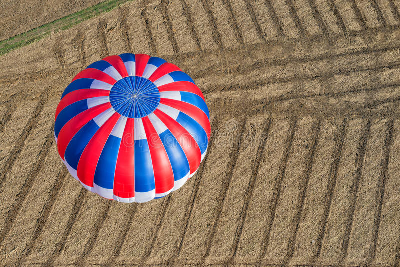 Aeriel view of a hot air balloon. Flying over a stripped field royalty free stock images