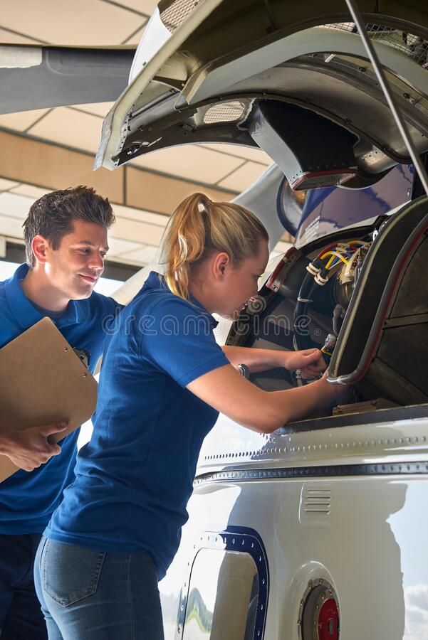 Aero Engineer And Apprentice Working On Helicopter In Hangar stock images