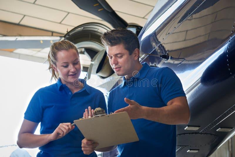 Aero- ingeniero And Apprentice Working en el helicóptero en hangar fotografía de archivo libre de regalías