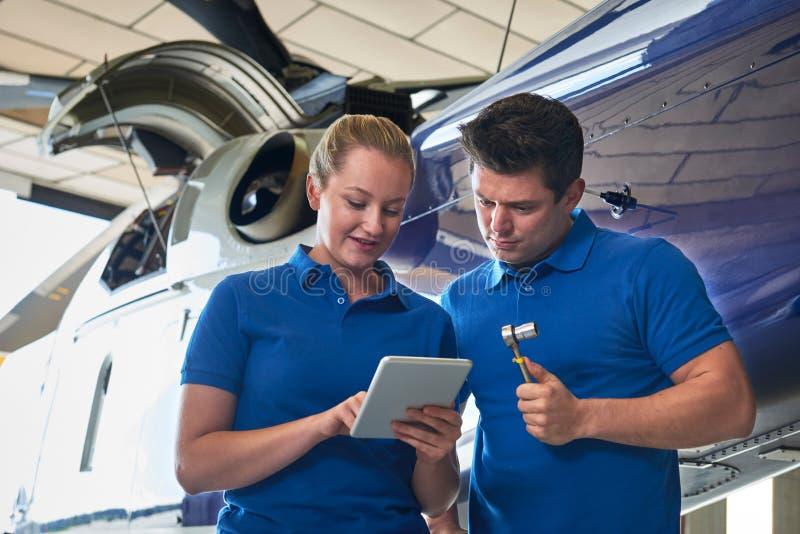 Aero- ingeniero And Apprentice Working en el helicóptero en retrete del hangar imágenes de archivo libres de regalías