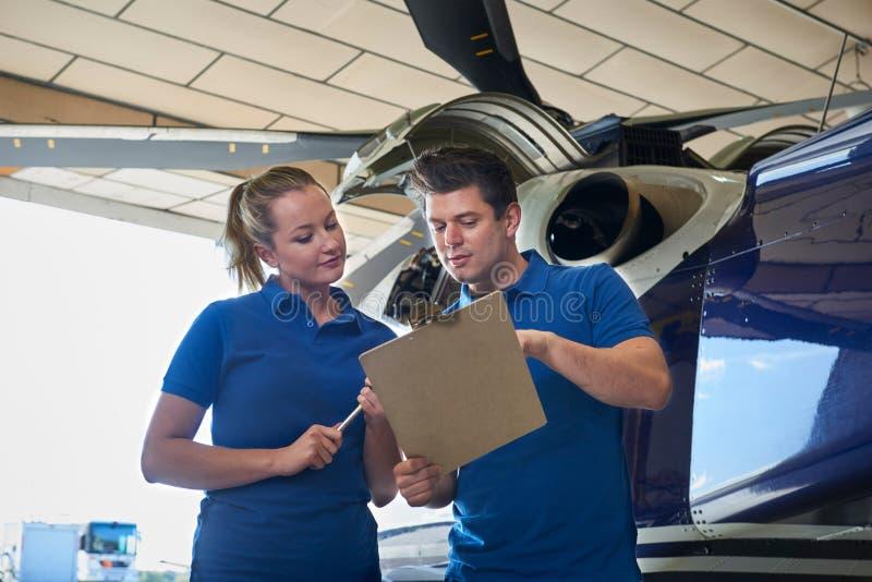 Aero- ingeniero And Apprentice Working en el helicóptero en retrete del hangar fotos de archivo libres de regalías