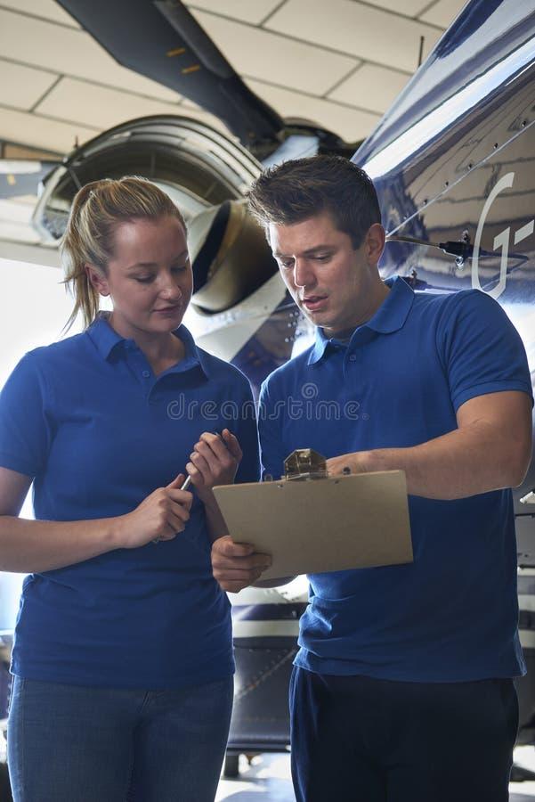 Aero- ingeniero And Apprentice Working en el helicóptero en retrete del hangar foto de archivo libre de regalías