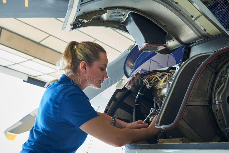 Aero- ingeniero de sexo femenino Working On Helicopter en hangar imagenes de archivo