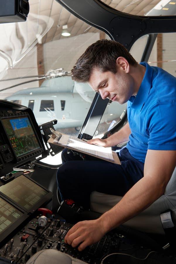 Aero- ingeniero de sexo masculino With Clipboard Working en carlinga del helicóptero fotografía de archivo libre de regalías
