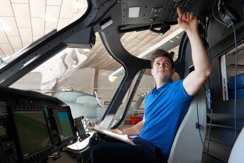 Aero- ingeniero de sexo masculino With Clipboard Working en carlinga del helicóptero foto de archivo