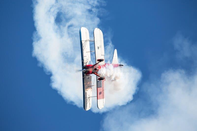 Aerobatic biplan wykonuje corkscrew manewr w głębokim niebieskim niebie obraz stock