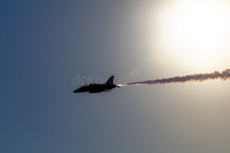 An aerobatic fast jet with smoke on is silhouetted against the sun stock photography