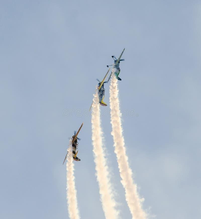 Aerobatic Piloten mit ihren farbigen Flugzeugen ausbildend im blauen Himmel stockbild