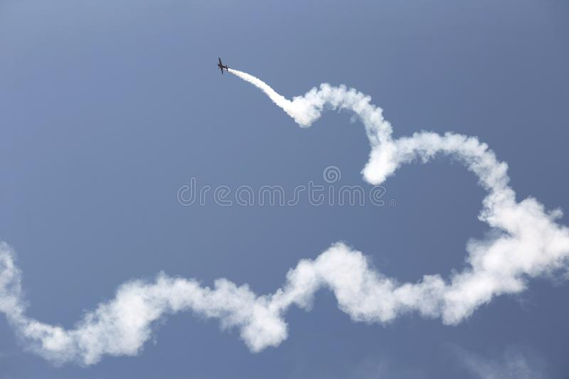 Aerobatic plane with a white smoke trail in sky. stock photo