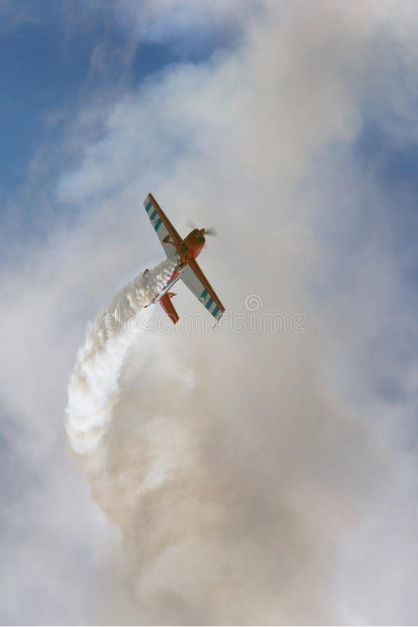 Aerobatic stunt plane. Low angle view of aerobatic stunt plane trailing smoke in cloudy sky stock images