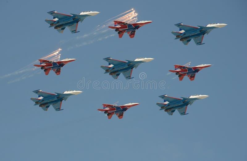 Aerobatic ` su-30cm och MiG-29 för ` för flygplan för ` för lag`-Swifts ` och för ` rysk riddaregjorde honnören under en repetiti arkivfoton